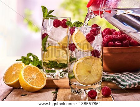 Alcohol drink. On wooden boards alcohol glasses with straw and ice cubes. Drink number hundred seventy four cocktail raspberry mojito with glass jug and pouring mohito. Outdoor. Light background.