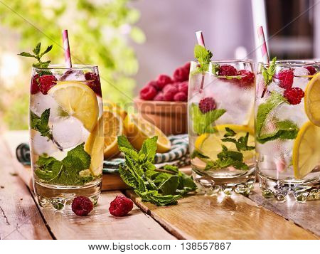 On wooden boards three glasses with ice cubes alcohol cocktail number hundred seventy seven raspberry cocktail mohito with straw and lime and mint leaf. Country life still. Light background.