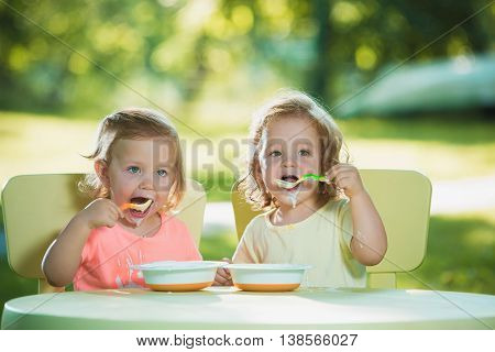 Two little 2 years old girls sitting at a table and eating together against a green lawn