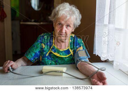 Elderly woman pensioner measures the blood pressure itself.