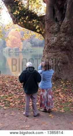 A Woman Standing Beside A Man Taking Photo