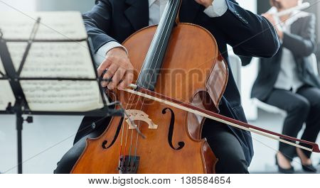 String section of classical music symphony orchestra performing cellist playing on foreground hands close up