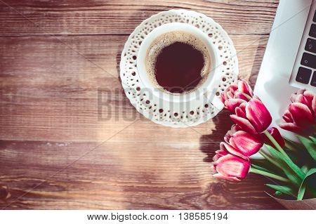 coffee cup, laptop and red flowers on wood table. vintage effect. top view.
