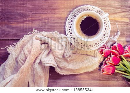A cup of black coffee and lovely flowers . Romantic background with retro filter effect.