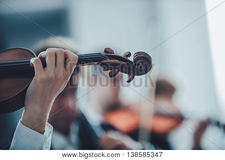 Female violinist performing and orchestra on background selective focus music and arts concept