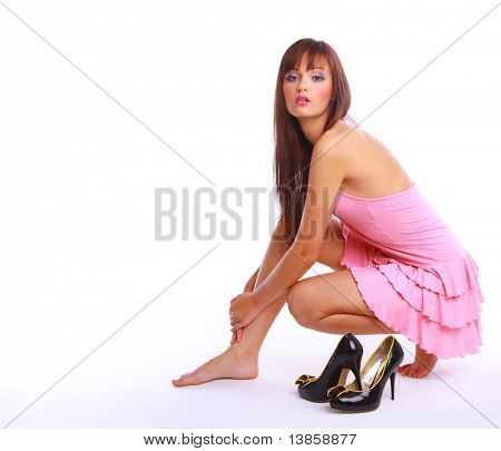Young beautiful woman wearing high heels sitting isolated on white background