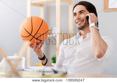 Lead active life. Cheerful handsome smiling man talking on cell phone and expressing joy while holding basket ball