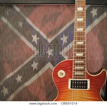 Southern Rock concept - detail close up of a guitar leaning against an amplifier with confederate rebel flag - vintage instagram filter applied