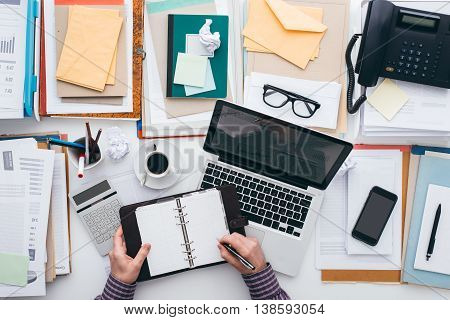 Businessman scheduling appointments on his organizer and full desktop with paperwork and a laptop flat lay