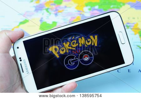 KOTA KINABALU, MALAYSIA - 16 JULY 2016: Hands holding a smart phone with screen Pokemon Go logo, a free-to-play augmented reality mobile game developed by Niantic for iOS and Android devices.
