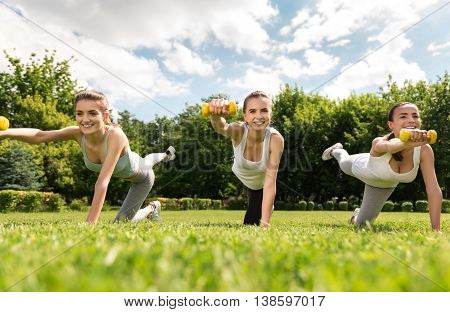 Move forward. Positive overjoyed smiling charming women holding dumbbells and doing sport exercises while expressing gladness