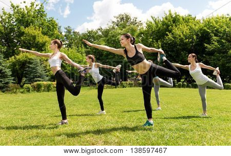 Activate your muscles. Pleasant delighted smiling women holding their legs and expressing positivity while doing sport exercises outside
