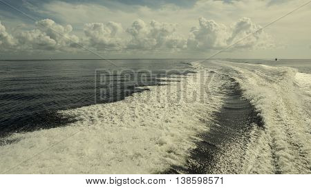 waves behind the boat on the sea with beautiful clouds. Nature composition Florida