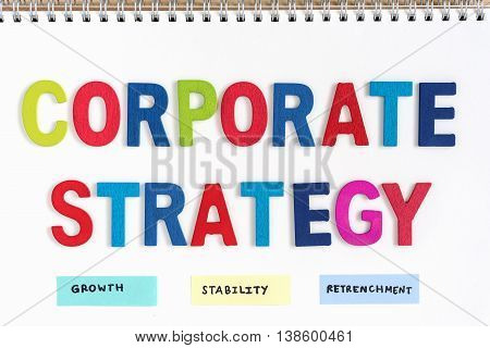 colorful letters wood words corporate strategy growth stability retrenchment on open notebook top view business concept