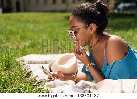 My leisure. Positive and content young woman texting someone using her mobile phone while lying on the grass in the park