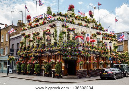 LONDON UK - 28TH JUNE 2016: A view of the outside of the Churchill Arms in London. Large amounts of flowers and UK decorations can be seen on the exterior.