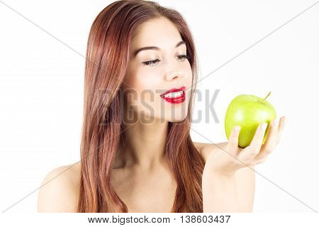 Portrait of beauty smiling woman looking at green apple. Healthy diet and nutrition. Smile with white teeth.