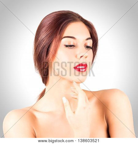 Portrait of sexy young woman with beautiful red lips looking down on gray background. Beauty woman with red lips touching chin.