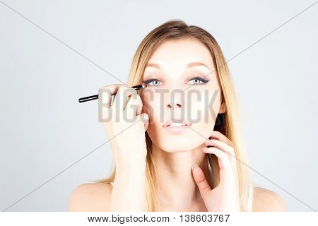 Blonde woman touching face and applying shadows on eye. Make up artist.