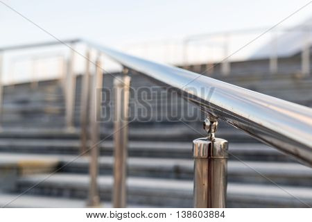 Public metal chrome handrail on gray staircase at city