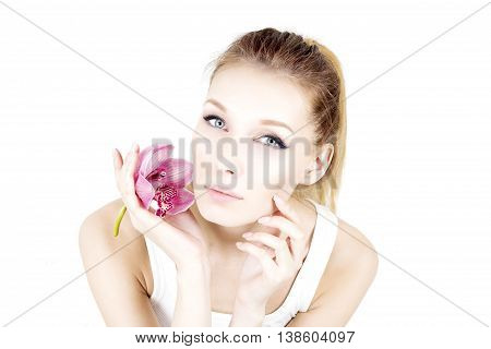 Portrait of woman with permanent make up holding pink flower and touching cheek.
