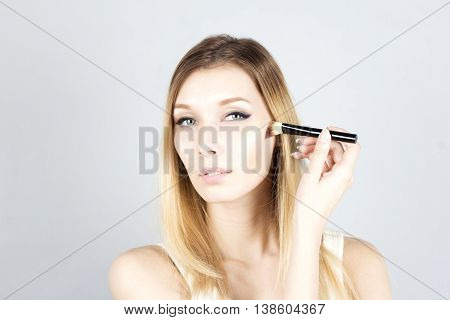 Young woman applying foundation with cosmetic brush. Make-up.