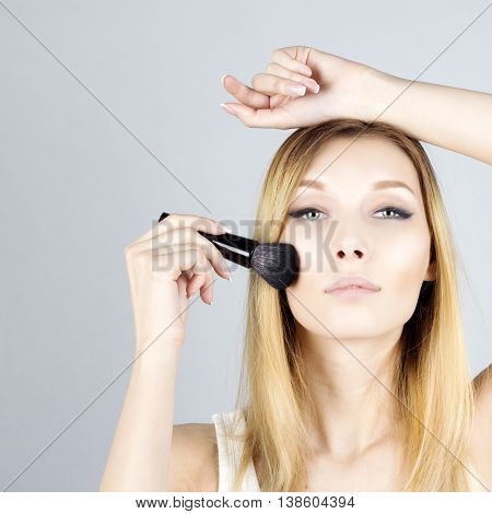 Portrait of beauty woman applying foundation with cosmetic brush. Make-up.