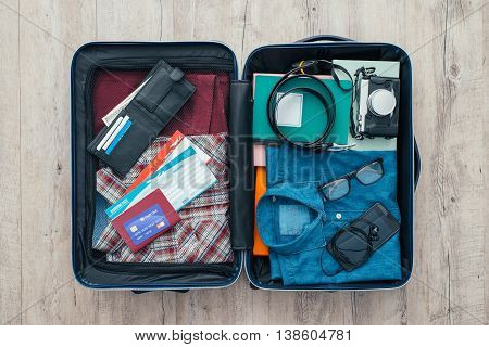 Open traveler's bag with clothing accessories credit card tickets and passport travel and vacations concept