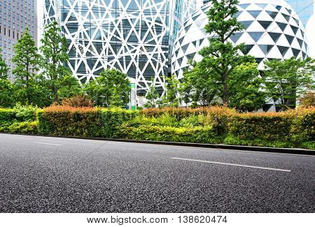 empty asphalt road by abstract buildings