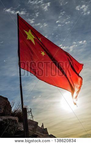 Flag of China at dawn on top of a mountain Huashan, China