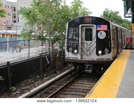 BROOKLYN, NEW YORK - JULY 9, 2016: NYC Subway Q Train arriving at Kings Highway Station in Brooklyn. Owned by the NYC Transit Authority, the subway system has 469 stations in operation
