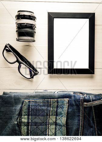 Blank Photo frame with Traveller equipment on wooden ackground.