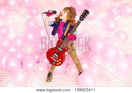 little girl singing a song with a microphone and a guitar on a background of pink balloons
