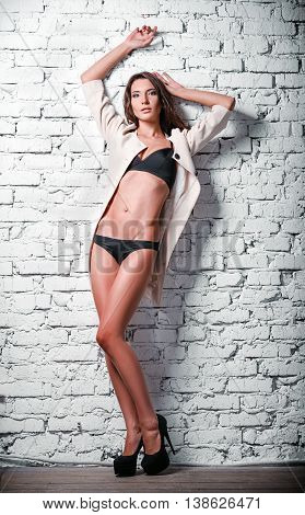 Fashion shot: a beautiful sexy young woman in lingerie and coat stands at brick wall. Full length