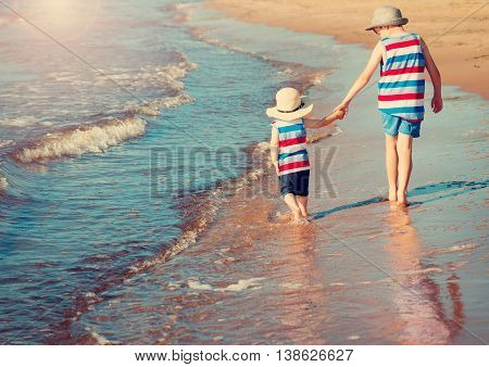 Two brothers barefoot are walking on the beach in water. Boys are on vacation in summer at the sea