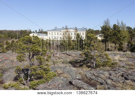 Yellow building beyond some small trees on the shore. Landmark, Post Museum built 1828 in Storby, Aland. Architects Carl Ludvig Engel and Carlo Bassi.