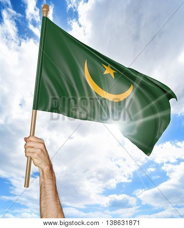 Person's hand holding the Mauritanian national flag and waving it in the sky, 3D rendering