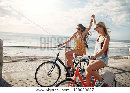 Female Friends Enjoying Cycling On A Summer Day