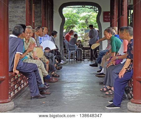 Chinese People Are Sitting In Pavilion, Park Of Chengdu