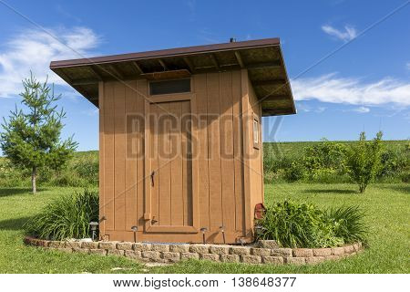 A wooden outhouse with landscaping in summer.