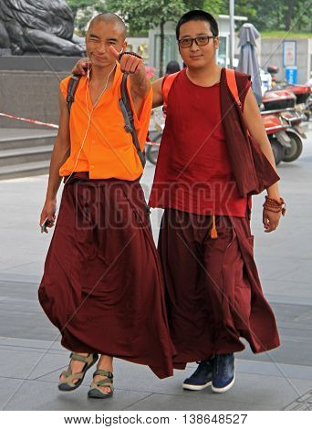 Two Chinese Monks Are Walking By Streets In Chengdu