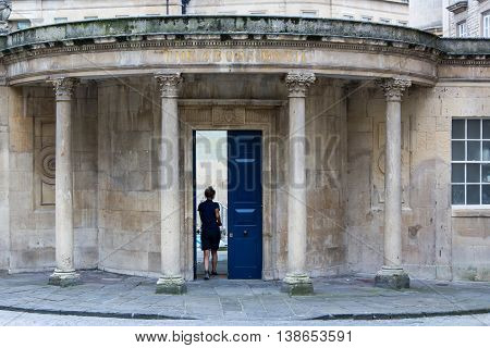 BATH SOMERSET UK - JULY 15 2016 Lady walking through door of The Cross Bath. Woman walks through door to spa and pool in the centre of the UNESCO World Heritage City of Bath