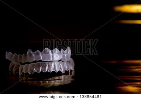 Invisible orthodontics on black background and gold