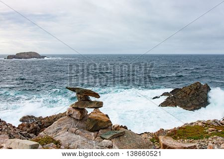 An Inukshuk and surf at the coast of Newfoundland