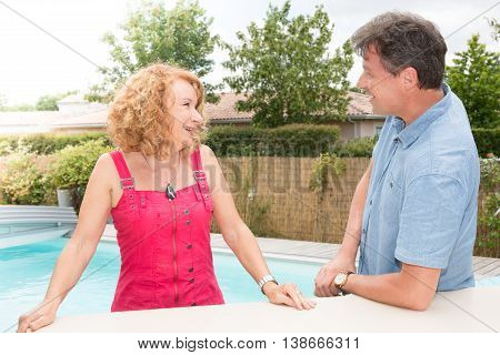 Cheerful Senior Couple Talking Cloe To The Swimming-pool