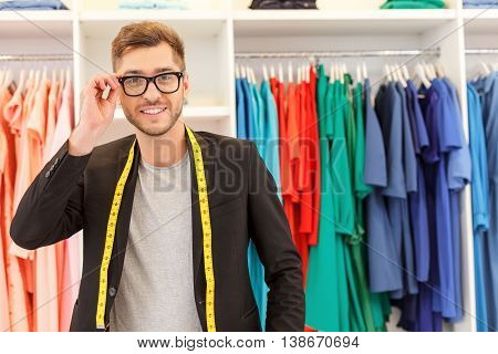 Skillful male designer is standing in workshop. She is looking at camera with confidence and adjusting glasses. Man is carrying tape measure on his neck and smiling