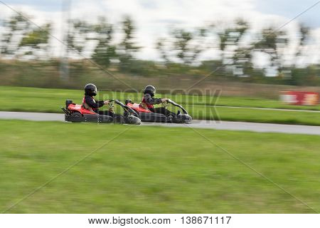 Super kart racing team. The racer on carting. Two Races on cartings. Races on a cross-country terrain. Cars races. Races on long exposure.
