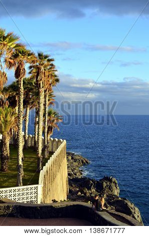 Callao Salvaje Tenerife Canary Islands Spain Europe - June 16 2016: A young couple sitting on a wall at Callao Salvaje coast in Adeje Tenerife