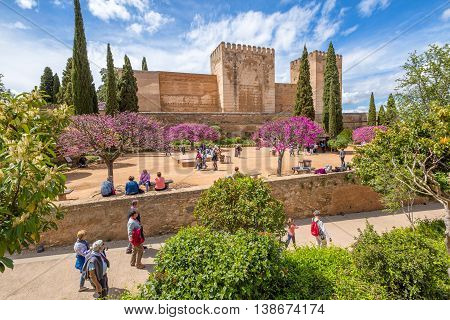 Granada, Andalucia, Spain - April 17, 2016: people and tourists around the Alcazaba de Granada, the military fortress of the Alhambra, in a sunny day.