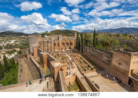 Alhambra de Granada, Spain - April 17, 2016: people and tourists visiting the Alcazaba de Granada, one of the most visited attractions of Andalusia. Aerial view from the tower of fortress.